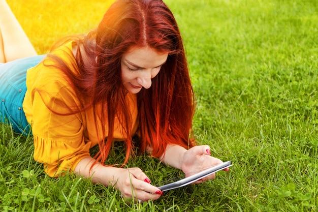 Linda garota, usando um computador tablet em um parque verde frondoso, navegando a tela sensível ao toque
