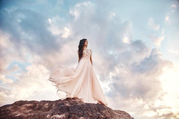 Linda garota usando um vestido de verão bege caminha montanhas