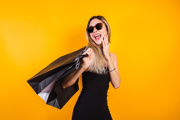 Linda garota usando um vestido preto com sacolas de compras pretas sobre fundo amarelo