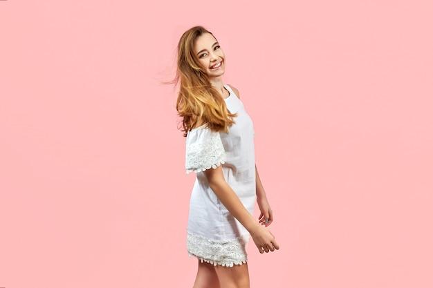 Linda garota usando vestido branco e posando em fundo rosa.
