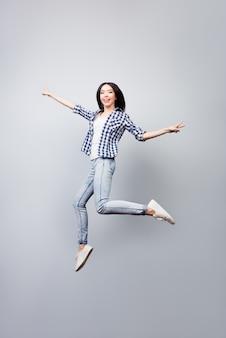 Linda garota vestida com camisa xadrez e jeans, pulando e mostrando vsign