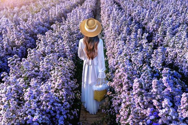 Linda garota vestida de branco caminhando nos campos de flores de margaret, em chiang mai, na tailândia