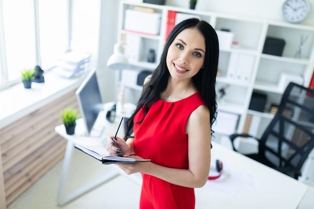 Linda garota vestida de vermelho está de pé no escritório e segurando um caderno e um lápis.