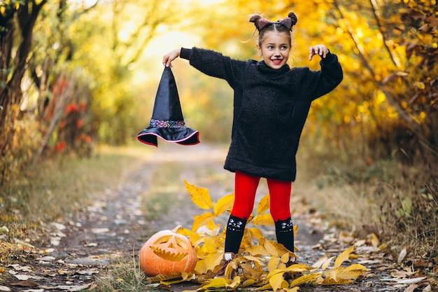 Linda garota vestida em traje de halloween ao ar livre com abóboras