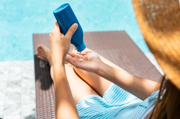 Linda garota vestindo maiô, aplicando protetor solar e relaxando à beira da piscina