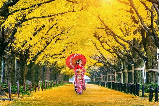 Linda garota vestindo quimono tradicional japonês na linha da árvore de ginkgo amarelo no outono. parque de outono em tóquio, japão.