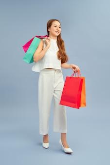 Linda garota vestindo roupas casuais em pé isolada sobre um fundo azul, carregando sacolas de compras