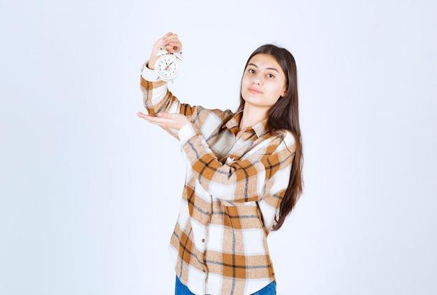 Linda garota vestindo roupas casuais, mostrando a hora no despertador.