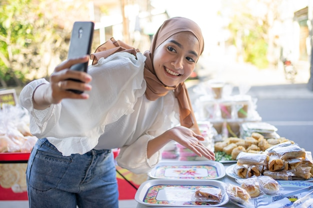 Linda garota vestindo um hijab sorridente e usando um telefone celular oferece uma variedade de alimentos fritos online
