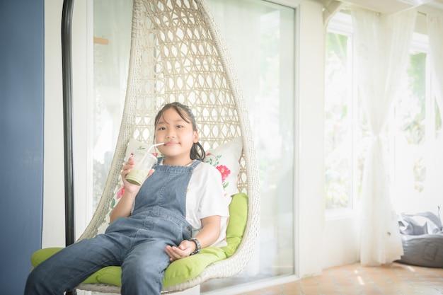Linda garota, vestindo um macacão jeans, está bebendo chá verde gelado e relaxa na casa branca. conceito de lazer e relaxamento