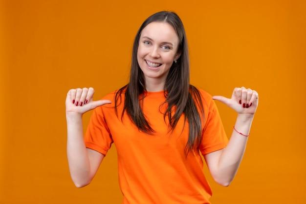 Linda garota vestindo uma camiseta laranja apontando para si mesma, satisfeita e orgulhosa, sorrindo em pé sobre um fundo laranja isolado