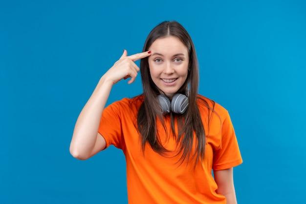Linda garota vestindo uma camiseta laranja com fones de ouvido apontando para a têmpora, lembrando-se de não se esquecer de nada importante, sorrindo em pé sobre um fundo azul isolado