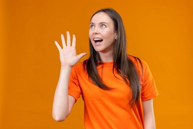 Linda garota vestindo uma camiseta laranja gritando ou chamando alguém com a mão perto da boca em pé sobre um fundo laranja isolado