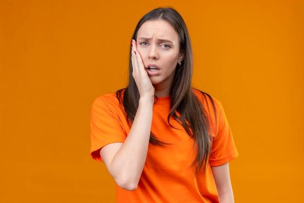Linda garota vestindo uma camiseta laranja, parecendo doente, tocando sua bochecha, sentindo dor de dente em pé sobre um fundo laranja isolado