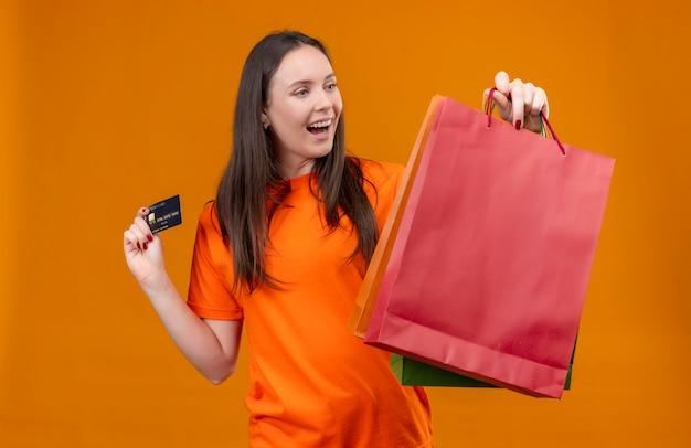 Linda garota vestindo uma camiseta laranja segurando um pacote de papel e um cartão de crédito, sorrindo alegremente em pé sobre um fundo laranja isolado