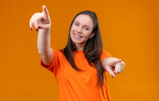 Linda garota vestindo uma camiseta laranja sorrindo feliz e positiva apontando com os dedos para a câmera em pé sobre um fundo laranja isolado