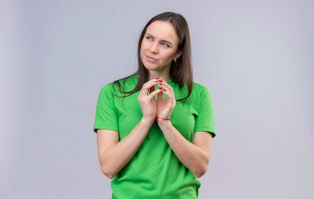 Linda garota vestindo uma camiseta verde de mãos dadas, olhando para o lado maliciosamente com uma expressão pensativa no rosto em pé sobre um fundo branco isolado