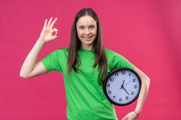 Linda garota vestindo uma camiseta verde segurando o relógio e sorrindo alegremente fazendo um sinal de ok em pé sobre um fundo rosa isolado