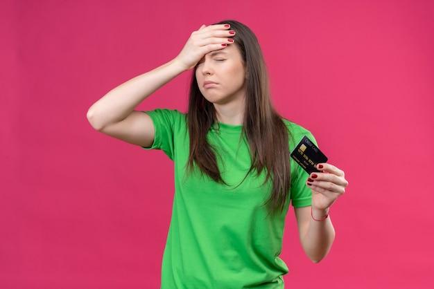 Linda garota vestindo uma camiseta verde segurando um cartão de crédito segurando sua cabeça com a mão por engano chateada com os olhos fechados em pé sobre um fundo rosa isolado