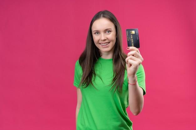 Linda garota vestindo uma camiseta verde segurando um cartão de crédito, sorrindo alegremente feliz e positiva em pé sobre um fundo rosa isolado
