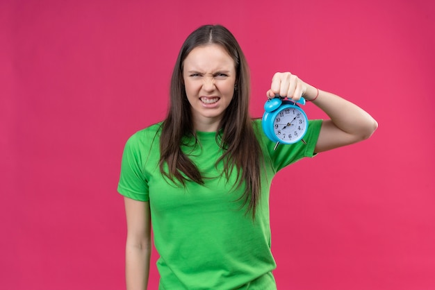 Linda garota vestindo uma camiseta verde segurando um despertador, olhando para a câmera com uma cara carrancuda e zangada em pé sobre um fundo rosa isolado
