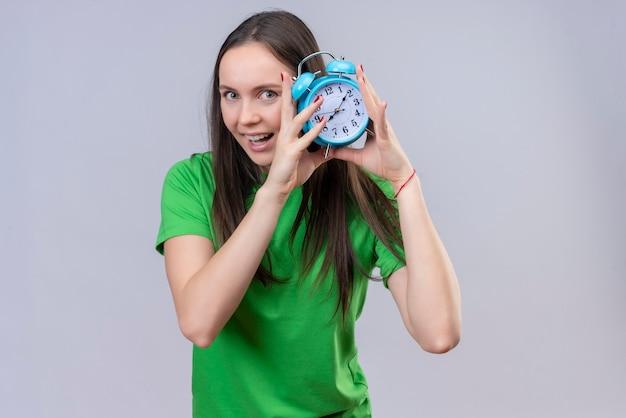 Linda garota vestindo uma camiseta verde segurando um despertador, olhando para a câmera, saindo e sorrindo feliz em pé sobre um fundo branco isolado