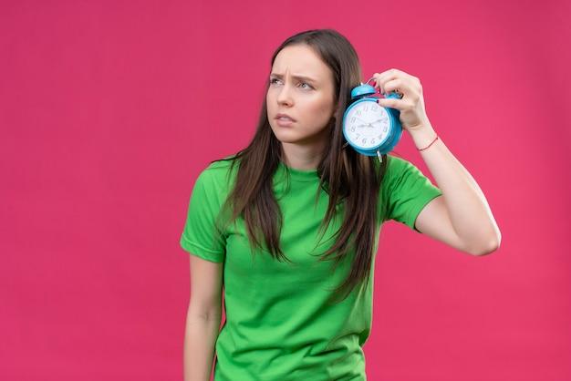 Linda garota vestindo uma camiseta verde segurando um despertador, parecendo confusa em pé sobre um fundo rosa isolado