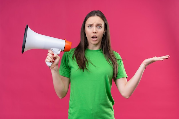 Linda garota vestindo uma camiseta verde segurando um megafone, abrindo os braços, parecendo confusa em pé sobre um fundo rosa isolado