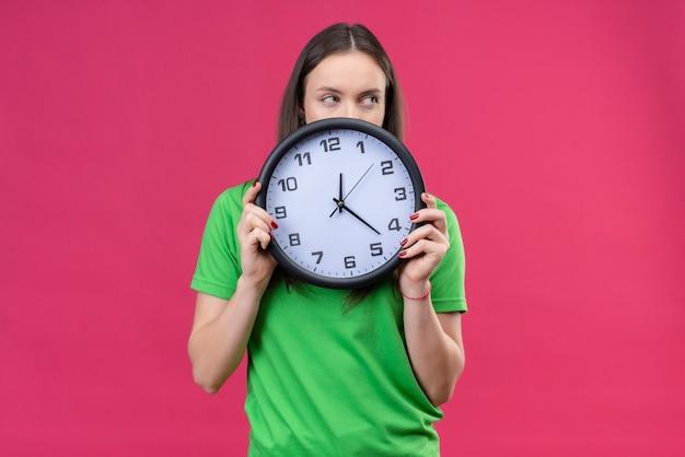 Linda garota vestindo uma camiseta verde segurando um relógio e olhando para ele, de pé sobre um fundo rosa isolado
