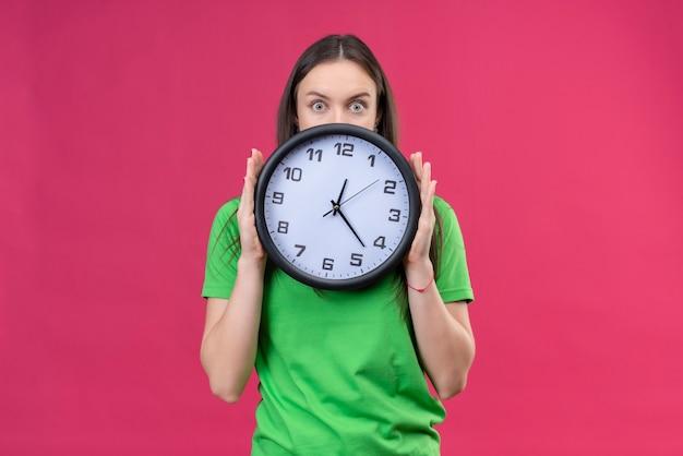 Linda garota vestindo uma camiseta verde segurando um relógio olhando por cima e parecendo surpresa em pé sobre um fundo rosa isolado