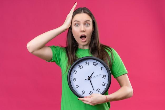 Linda garota vestindo uma camiseta verde segurando um relógio parecendo espantada e surpresa tocando a cabeça com a mão em pé sobre um fundo rosa isolado