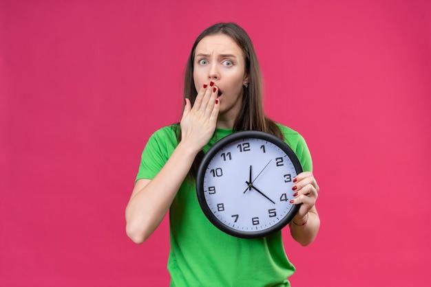 Linda garota vestindo uma camiseta verde segurando um relógio parecendo surpresa e chocada, cobrindo a boca com a mão em pé sobre um fundo rosa isolado