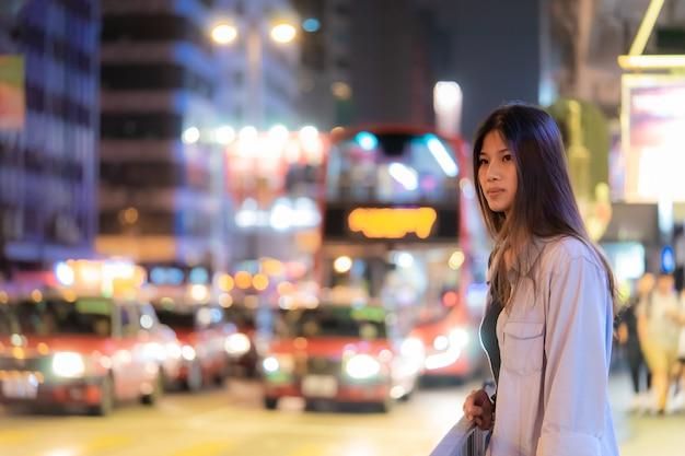 Linda garota viajante asiática na rua à noite de hong kong