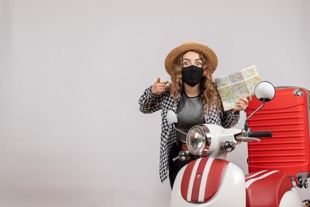 Linda garota viajante com máscara preta segurando um mapa em pé perto da motocicleta vermelha