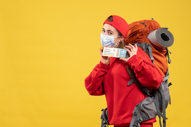Linda garota viajante com mochila e máscara segurando o tíquete de frente