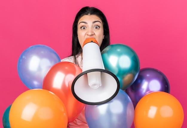 Linda garota zangada atrás de balões falando no alto-falante