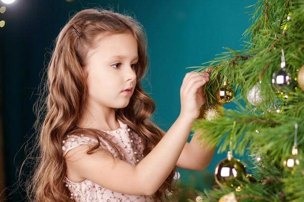 Linda garotinha a decorar a árvore de natal em casa