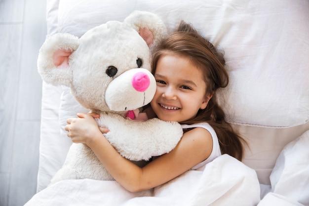Linda garotinha abraçando seu ursinho de pelúcia na cama