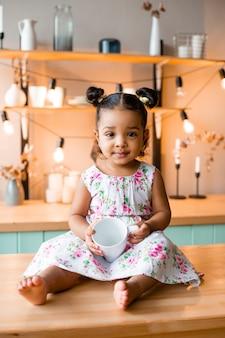 Linda garotinha afro-americana em casa na cozinha