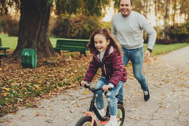 Linda garotinha andando de bicicleta enquanto seu pai está tentando pegá-la rindo ao ar livre no parque.