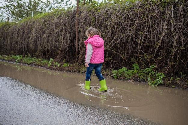 Linda garotinha andando na rua e em botas de borracha verde em poças atirando por trás. a garota está andando de botas e pé torto. o problema com os pés, doença dos pés.