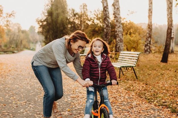 Linda garotinha aprendendo a andar de bicicleta no parque com a mãe.