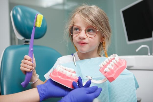 Linda garotinha aprendendo a escovar os dentes no escritório da debntist em uma modelo de mandíbula grande