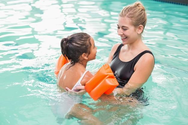 Linda garotinha aprendendo a nadar com treinador
