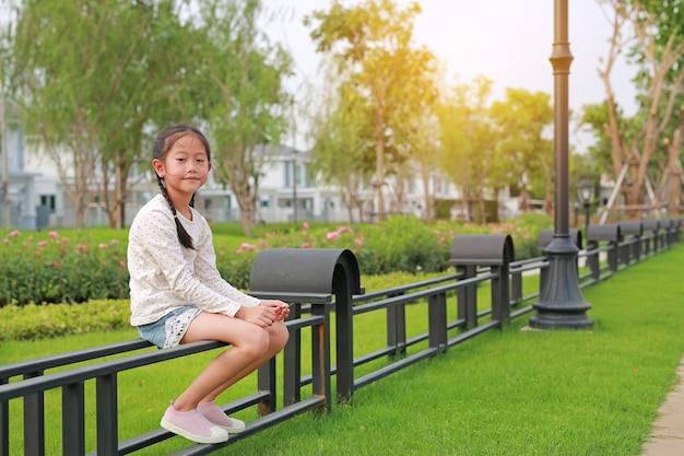 Linda garotinha asiática sentada no jardim em cima da cerca em um parque público ao ar livre