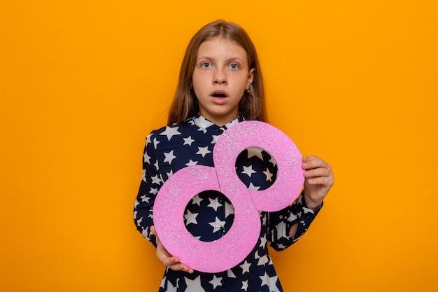 Linda garotinha assustada no feliz dia da mulher segurando o número oito