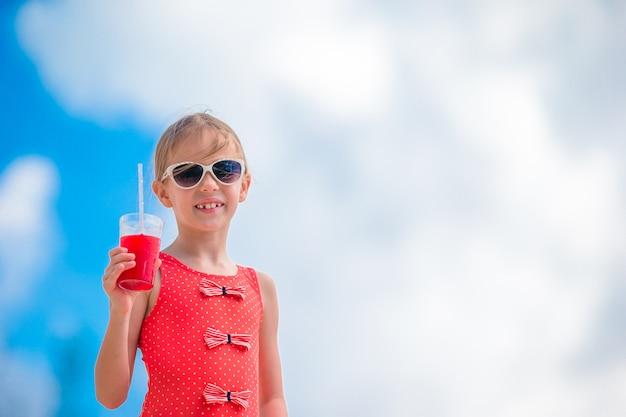 Linda garotinha beber cocktails na praia tropical