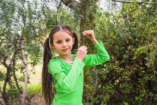 Linda garotinha brincando com galho olhando para a câmera