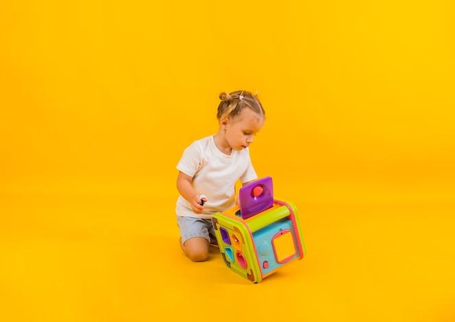 linda garotinha brincando com um grande brinquedo educacional em um fundo amarelo com espaço para texto