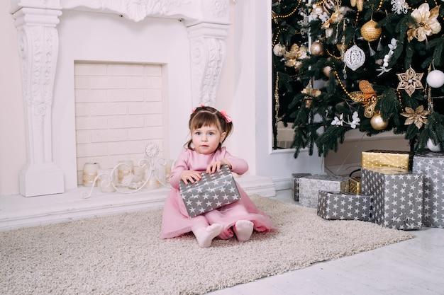 Linda garotinha brincando com um presente de natal